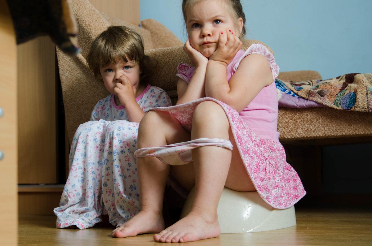 Маленькие девочки сидят на горшке