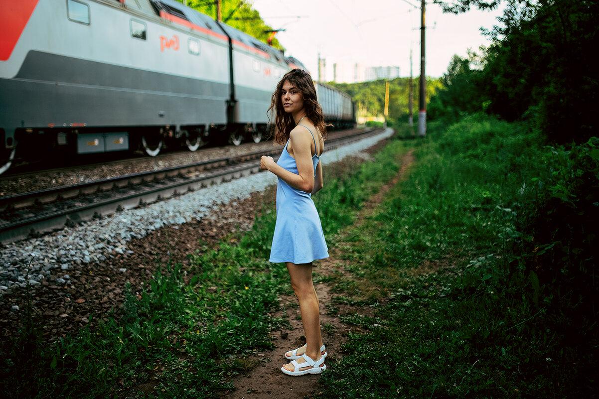 Девушка в голубом платье стоит на тропинке мимо проезжающего поезда в лесу - Lenar Abdrakhmanov