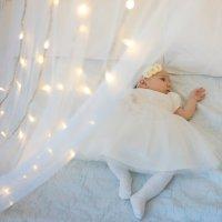 Малышка на кровати с новогодними огоньками в белом платье :: Ирина Вайнбранд