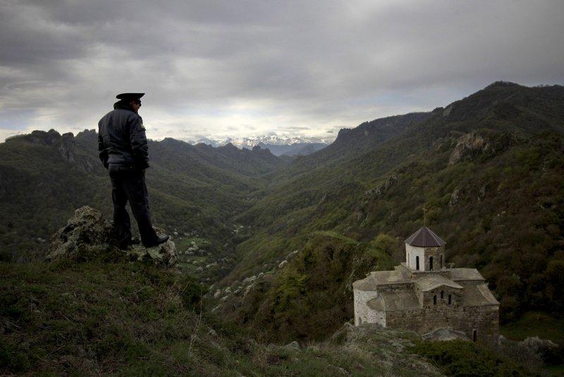 «На земле и в небесах». Автор фото: Валерий Мельников. Сотрудник милиции охраняет храм в горах Карачаево-Черкесии, Россия.