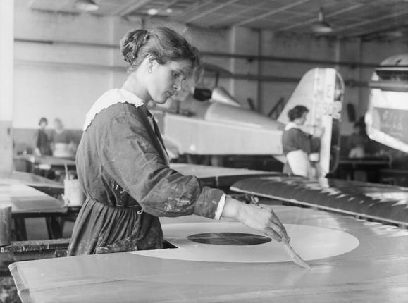 Неизвестный автор. Женщина, рабочая фабрики «Austin Motor Company» в Бирмингеме, рисует круг на крыле самолета «SE5A». Сентябрь 1918. Собрание Имперского военного музея, Лондон